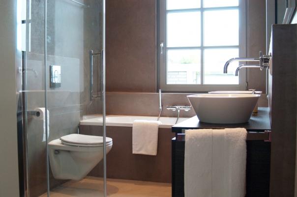 Badkamer, woonhuis Oirschot. VERBAU-betonstuc. Op de wanden en badombouw kleur #06, lichte rivierklei, op de vloer #12, kiezelgrijs.